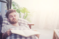 Man reading book with holding hand sleep in couch sofa. Royalty Free Stock Photo