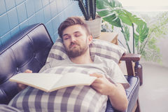 Man reading book with holding hand sleep in couch sofa. stock image