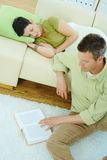 Man reading book at home. Young couple resting at home. Man reading book on floor, woman sleeping on couch Royalty Free Stock Photography