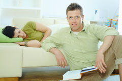 Man reading book at home. Young couple resting at home. Man reading book on floor, woman sleeping on couch Stock Image