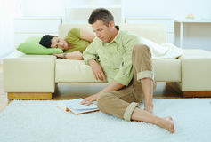 Man reading book at home. Young couple resting at home. Man reading book on floor, woman sleeping on couch Stock Photography