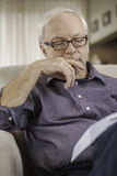Man reading a book at home. Relaxed senior man reading a book on the sofa at home Stock Photos