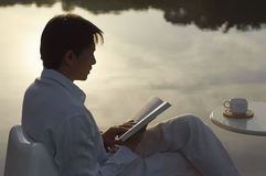Man reading book beside lake in morning royalty free stock photo