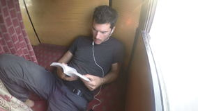 Man reading a book while laying in train cabin during ride, time lapse. MUMBAI, INDIA - 4 FEBRUARY 2015: Man reading a book while laying in train cabin during stock footage