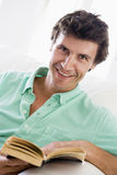 Man reading book in living room smiling. At camera Royalty Free Stock Photography