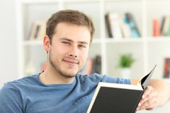 Man reading a book looking at you Royalty Free Stock Photo