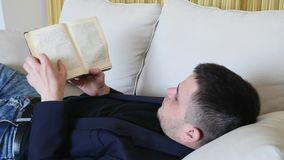 Man reading a book lying on the couch and dreams stock video