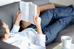 A man reading book while lying on the couch Stock Image