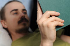 Man reading book lying Royalty Free Stock Photo