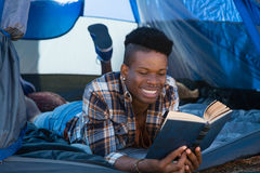 Man reading book while lying in the tent Royalty Free Stock Photos