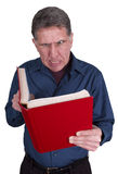 Man Reading Book Mad Angry Isolated on White. Middle aged man who is mad or angry reading a book. There is data or information that this male is finding to be Stock Photo