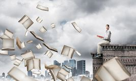Man reading book and many of them flying in air Royalty Free Stock Image