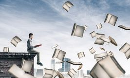 Man reading book and many of them flying in air Stock Images
