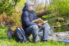 Man reading book in meadow near river Royalty Free Stock Images