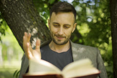 Man reading book about modern psychology Stock Image
