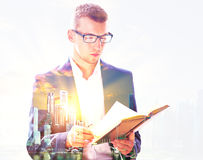 Man reading book multiexposure. Young businessman in glasses reading book on abstract city background with sunlight. Double exposure Stock Photography
