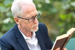 Man reading a book outdoors. Mature man reading a book outdoors stock image