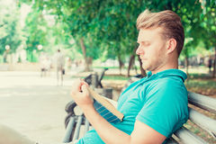 Man reading a book in a park. On summer sunny day Stock Photo