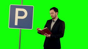 Man reading a book with parking sign on a Green. Screen, Chroma Key. Professional shot on BMCC RAW with high dynamic range. You can use it e.g in your stock video footage