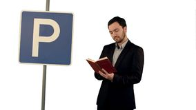 Man reading a book with parking sign on white background isolated. Professional shot on BMCC RAW with high dynamic range. You can use it e.g in your commercial stock photos