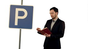 Man reading a book with parking sign on white. Background isolated. Professional shot on BMCC RAW with high dynamic range. You can use it e.g in your commercial stock video footage