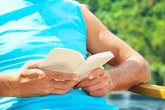 Man reading  book poolside Royalty Free Stock Image
