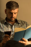 Man reading book. Portrait of man reading book and drinking wine Royalty Free Stock Photos