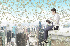 Man reading a book on the roof. A young man sitting on the edge of the roof and reading a book, money falling from above. Side view. New York at the background Stock Photos