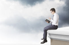 Man reading a book on the roof. A young man sitting on the edge of the roof and reading a book. Side view. Dark clouds at the background. Concept of studying Stock Image