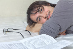 Man reading a book while he's lying on bad Stock Photo