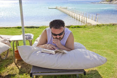 Man is reading a book at the sea Royalty Free Stock Photography