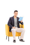 Man reading a book seated in an armchair Stock Image