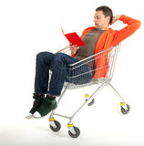 Man reading book in shopping cart Royalty Free Stock Photos
