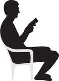 Man reading a book silhouette. Man reading a book on the chair silhouette Stock Photography