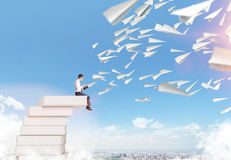 Man reading book. Man sitting on cloud reading, paper planes flying from book. Blue sky and city at  background. Paris. Concept of reading Royalty Free Stock Image