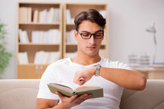 The man reading book sitting in couch sofa Stock Photo