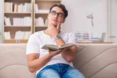 The man reading book sitting in couch sofa Royalty Free Stock Photography