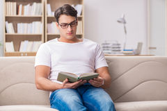 The man reading book sitting in couch sofa Stock Photos