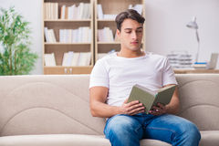 The man reading book sitting in couch sofa Stock Images