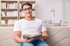 The man reading book sitting in couch sofa Stock Photography