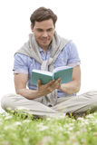 Man reading book while sitting on grass against sky Royalty Free Stock Images