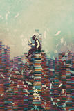 Man reading book while sitting on pile of books,