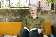 Man reading a book in sofa bed outdoors Royalty Free Stock Images