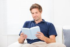 Man Reading Book On Sofa Royalty Free Stock Photography