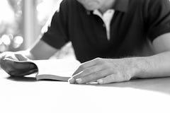 A man reading book on the table Stock Photos