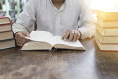 Man reading book with textbook stack on wooden desk. In library Royalty Free Stock Photos