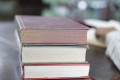 Man reading book with textbook stack on wooden desk Royalty Free Stock Photography