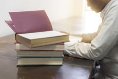 Man reading book with textbook stack on wooden desk Stock Photos