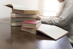 Man reading book with textbook stack on wooden desk Stock Images