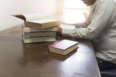 Man reading book with textbook stack on wooden desk Stock Photography